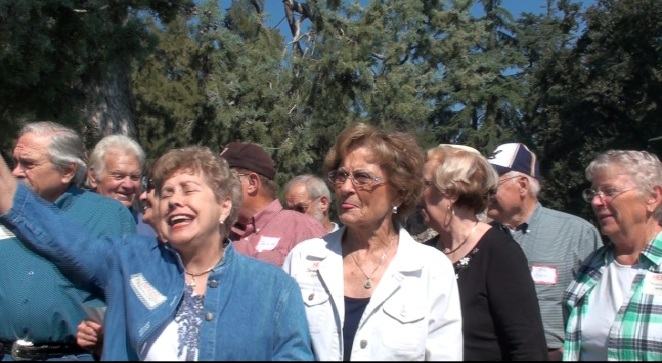 Peggy Serbu Johnson giving the Eeeaah-tau yell with Mary Louise Burr Akin and Caroline Nelson McFall in the foreground